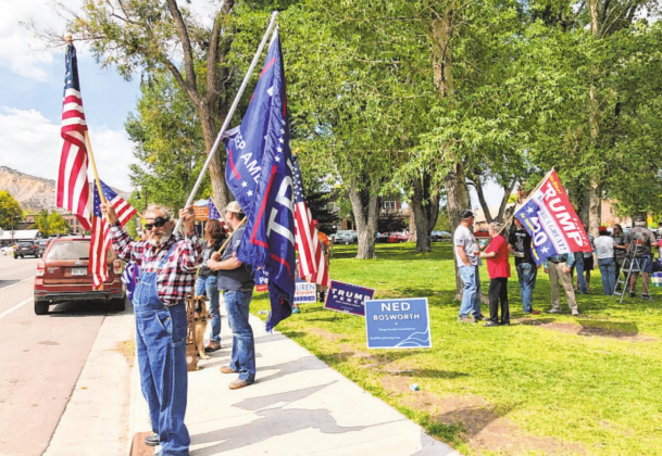 "Ouray County resident Ray Brunacini holds a U.S. flag and a flag supporting President Donald Trump next to Hartwell Park in Ridgway on Saturday. A ""Freedom Rally"" at the park drew about 30 attendees. Liz Teitz — Ouray County Plaindealer"