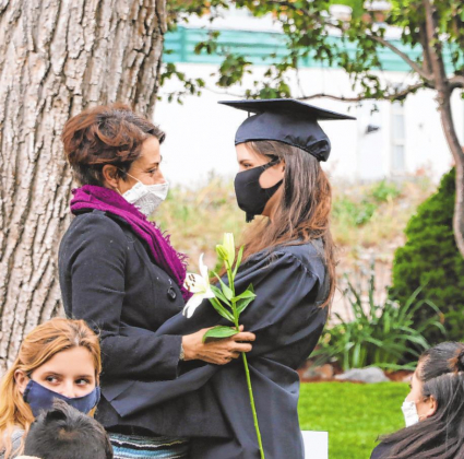 Graduate Josefine Dannecker-Evans presents family with lilies at her graduation on Sunday, in Fellin Park. The graduates traditioanlly give flowers to loved ones, friends and mentors during the graduation ceremony.