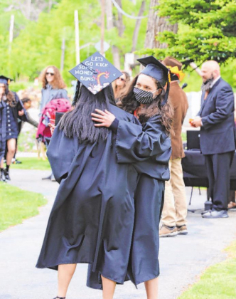 Ouray High School Class of 2020 valedictorian Anna Biolchini hugs salutatorian Genevieve McArdle after the graduation ceremony at Fellin Park.