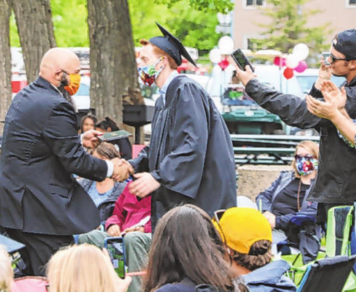 Below right: Ouray School District Lead Administrator Kenneth Nelson ongratulates and hands a diploma to graduate Judah Preston.