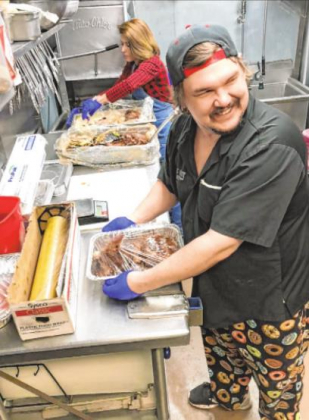 True Grit Cafe owner Tammee Tuttle and kitchen manager Robert Collins prepare several pot roast meals as togo orders on Tuesday. Mike Wiggins — Ouray County Plaindealer