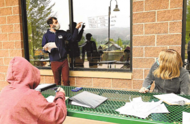 Trevor Peterson teaches an eighth grade math and science class outside Ridgway Secondary School. To allow for social distancing and air flow, many teachers at the school are teaching classes outside, using windows as whiteboards and clipboards and picnic tables for desks. Liz Teitz-Ouray County Plaindealer