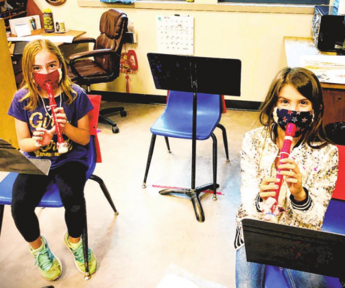 Ouray School fourth graders Imogene Demuth and Mikayla Hurt play recorders in music class wearing masks made by high school art students. The custom layered masks have a slit for the instrument's mouthpiece, and fabric is also wrapped around the end of the recorder to limit the spread of airborne particles that could carry the coronavirus. Photo courtesy Karisa Hoover