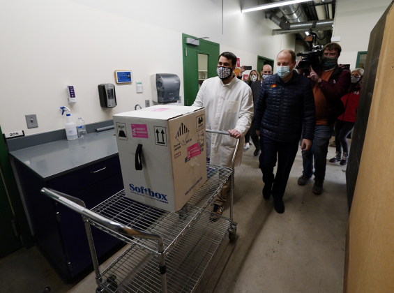 Colorado Governor Jared Polis, right, trails the cart bearing the state's first shipment of COVID-19 vaccine to a freezer with Patrick Belou, logisitics specialist at the laboratory for the Colorado Department of Public Health and Environment, early Monday, Dec. 14, 2020, in Denver. (AP Photo/David Zalubowski)