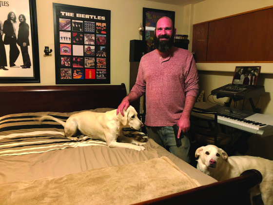 Kenny Easton stands with his dogs, Mattis and Ivan, in his bedroom in the spot where he discovered an intruder pointing a gun at him on Dec. 27. Easton holds the handgun he was carrying that night. Plaindealer photo by Erin McIntyre