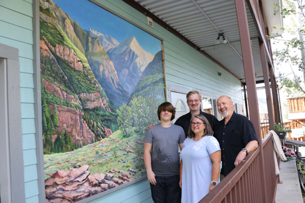 From left: Finn, Barthold and Cat Lichtenbelt celebrate the unveiling of the new mural adorning their building at 615 Clinton St., painted by Ridgway artist Edward Cating, who stands on the right. The Lichtenbelts decided to commission the painting of Mt. Abram and the Uncompahgre Gorge on the side of the building, where patrons of Kate's Restaurant can enjoy it from the patio. Plaindealer photo by Erin McIntyre