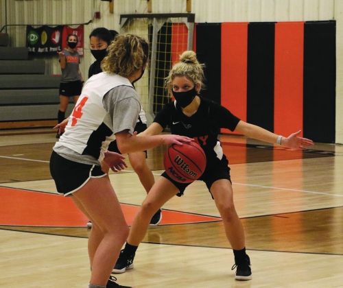 "Senior Haley Kunz guards junior Aynsleigh Wood in the Ouray girls basketball team's first practice on Monday. Sophomore Pallen McArdle provides the ""help"" defense. Assistant Coach Brittany Kunz directs the action. Erin McIntyre — Ouray County Plaindealer"