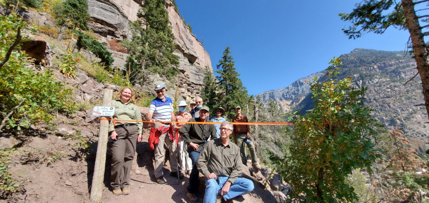 Mayor Greg Nelson sits in front of members of the Ouray Trail group and Ouray District Ranger Dana Gardunio (left) at the Oct. 6 ribbon cutting ceremony for the final section of the Ouray Perimeter Trail. Courtesy photo